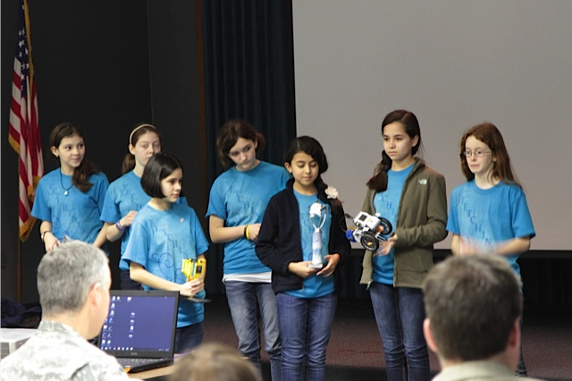 Middle School Lego League Team show off their trophy and robots